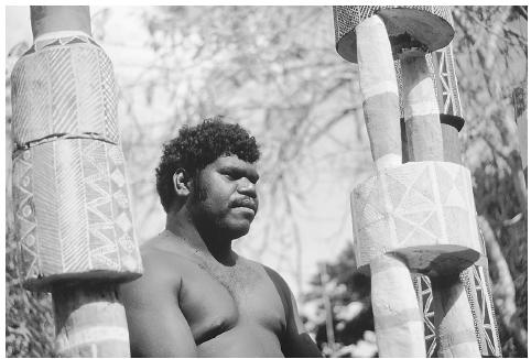 An Aborigine from the Tiwi tribe in Bathurst, New South Wales, Australia, stands beside painted funeral totems. Phases of funerary rites are often explicitly devoted to symbolic acts that send ancestral spirits back to their places of origin where they assume responsibility for the wellbeing of the world they have left behind. CHARLES AND JOSETTE LENARS/CORBIS