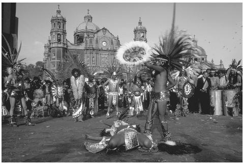A group of men in front of the Basilica of Our Lady of Guadalupe in Mexico perform an Aztec dance during the feast of the Virgin of Guadalupe on December 12, the most important religious holiday in Mexico. Here they reenact the prepara tion of a sacrifice, a recognition of the inextricable interdependence of life and death to the Aztec. SERGIO DORANTES/ CORBIS