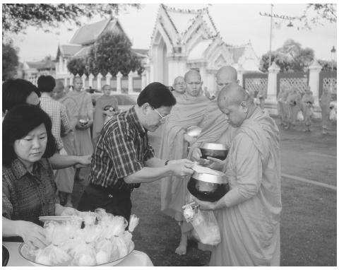 Buddhist Monks collect alms in Bangkok, Thailand. The Buddhist faith, which stresses the awareness of suffering and death, originated in sixth and fifth century B.C.E. India and then spread to Tibet, Asia, China, Korea, and Japan. CORBIS