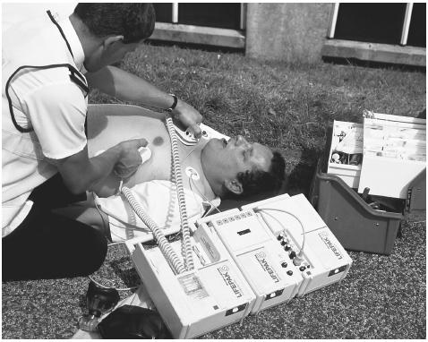 Attempting to save a heart attack victim, this paramedic uses a defibrillator machine that applies an electric shock to restore a regular heartbeat. PHOTO RESEARCHERS, INC.
