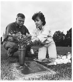 A grieving couple in Warminster, Pennsylvania, arranges flowers at the grave of their teenage son who was killed during a video store robbery. Couples with strong marital relationships prior to their child